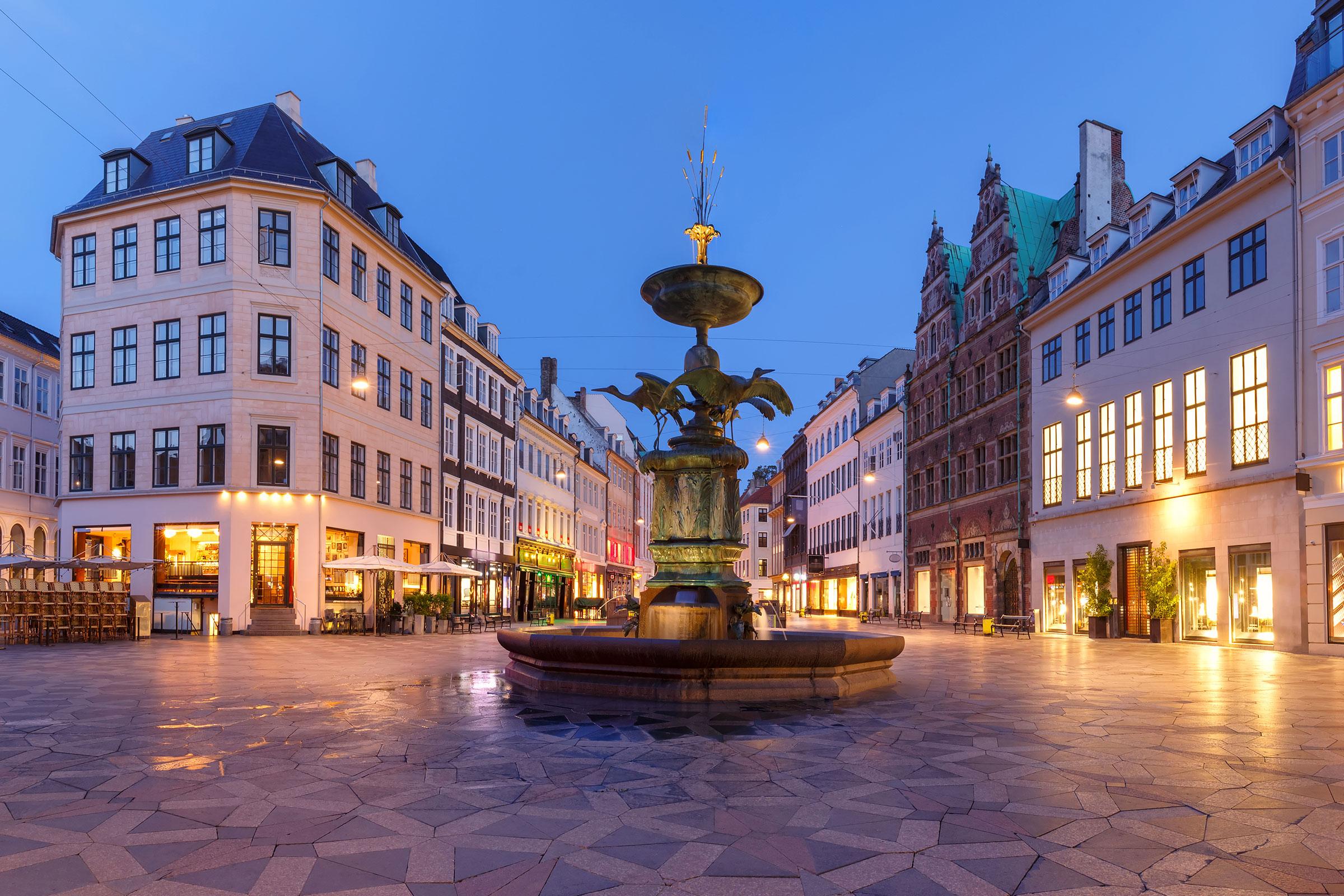 Stork Fountain on the Amagertorv square, Stroget street during morning blue hour, Copenhagen, capital of Denmark