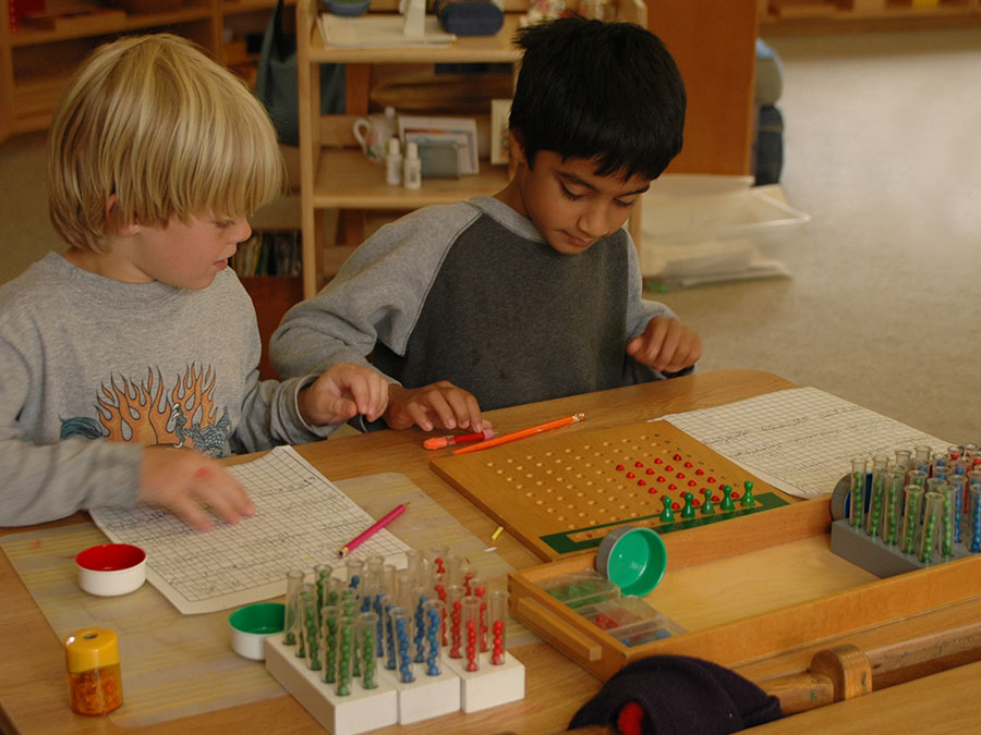 Boys engaged in Montessori maths materials