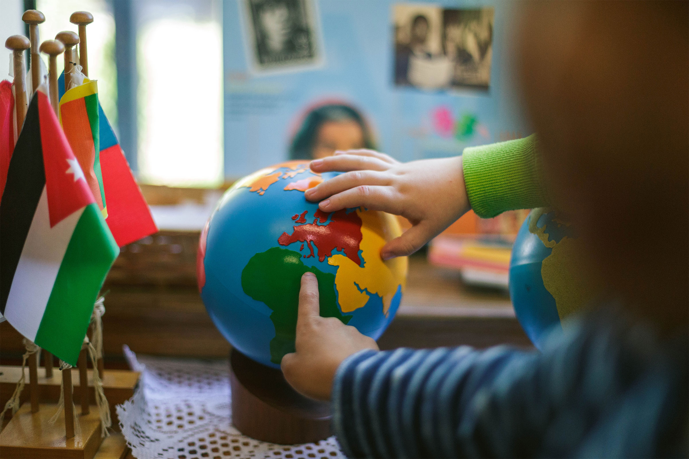 Children's hands pointing to globe of the world next to flags in Montessori classroom