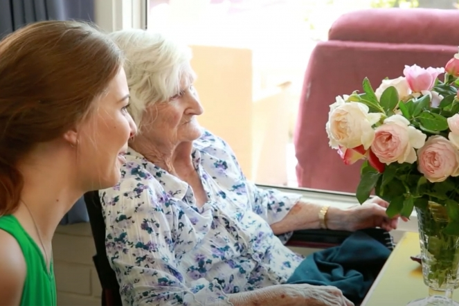 Elderly woman and female carer looking at a floral arrangement
