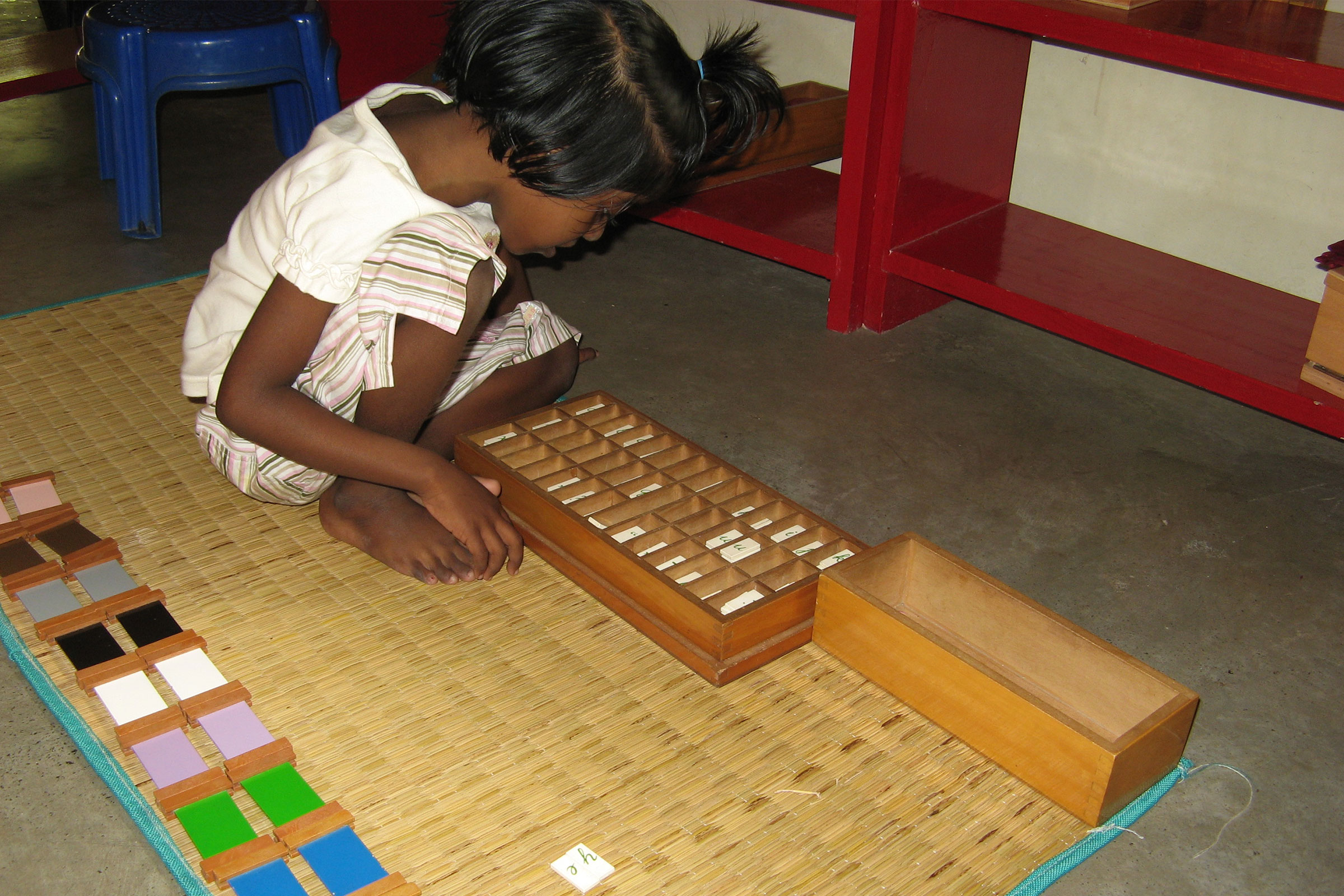 Child working on Montessori Moveable Alphabet material