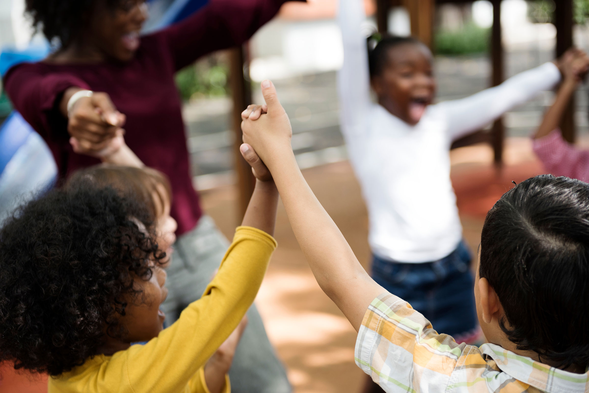 Circle of happy children with raised joined hands
