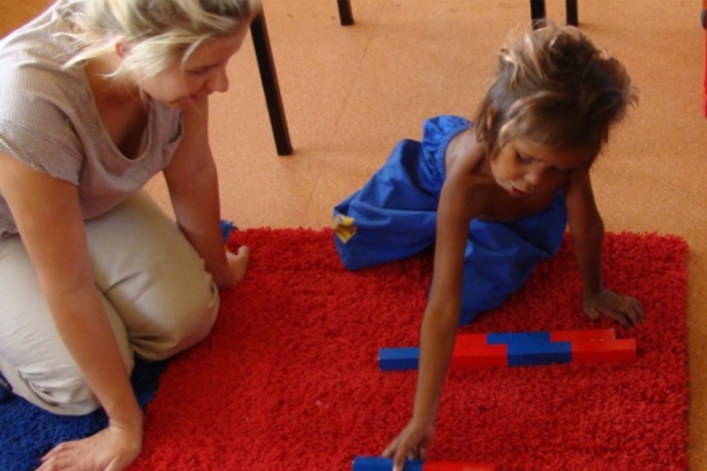 Montessori teacher with young child and maths materials