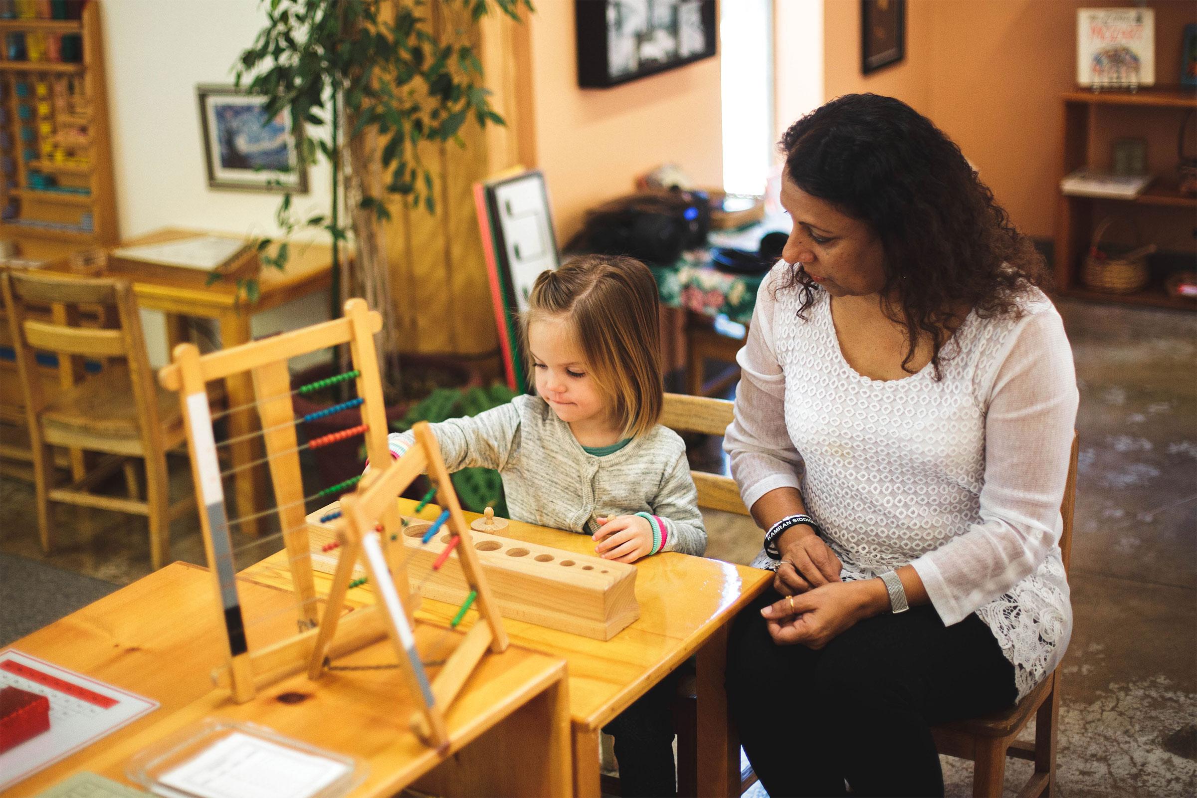 Directress watches child using Montessori materials