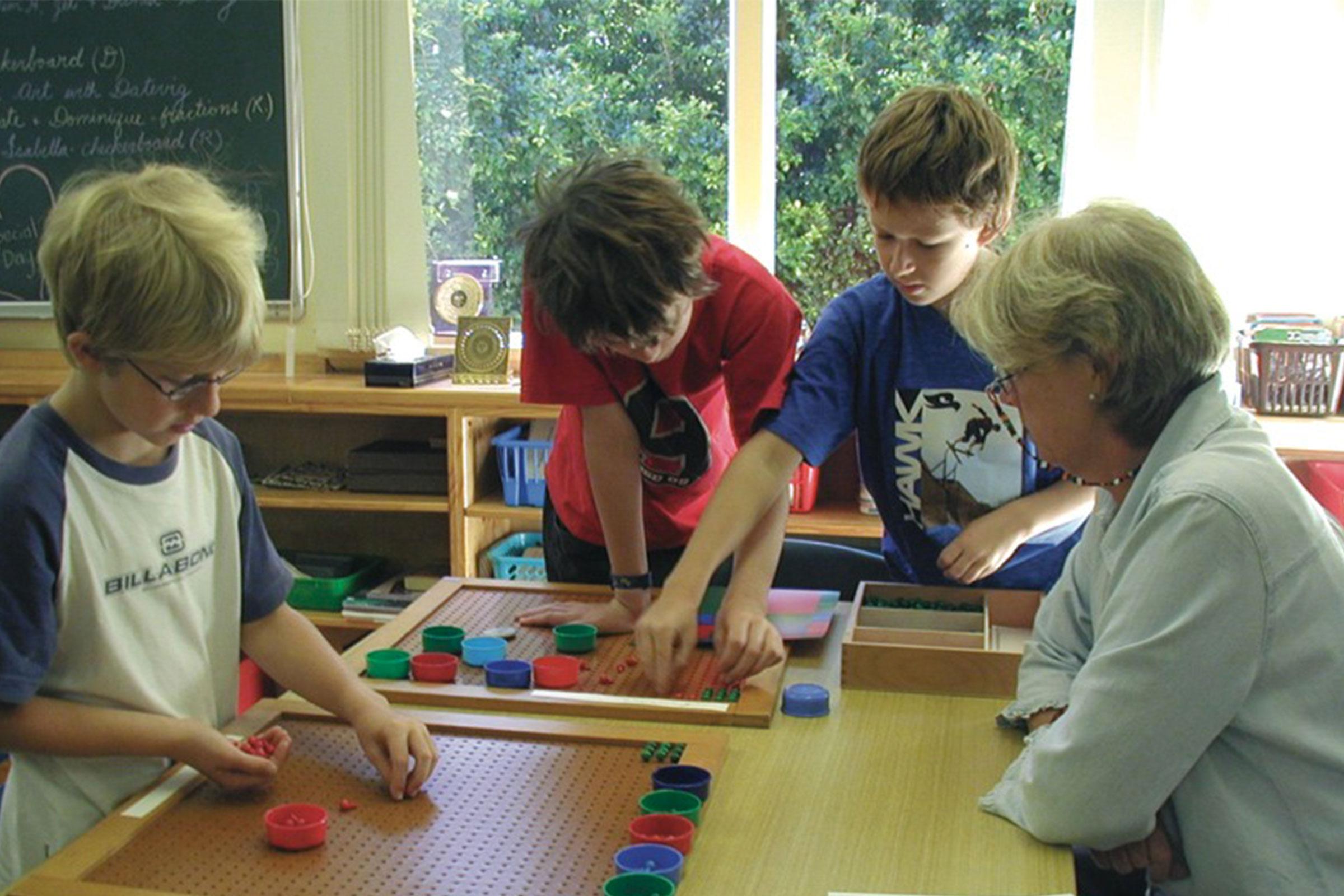 Montessori teacher observing group of primary children