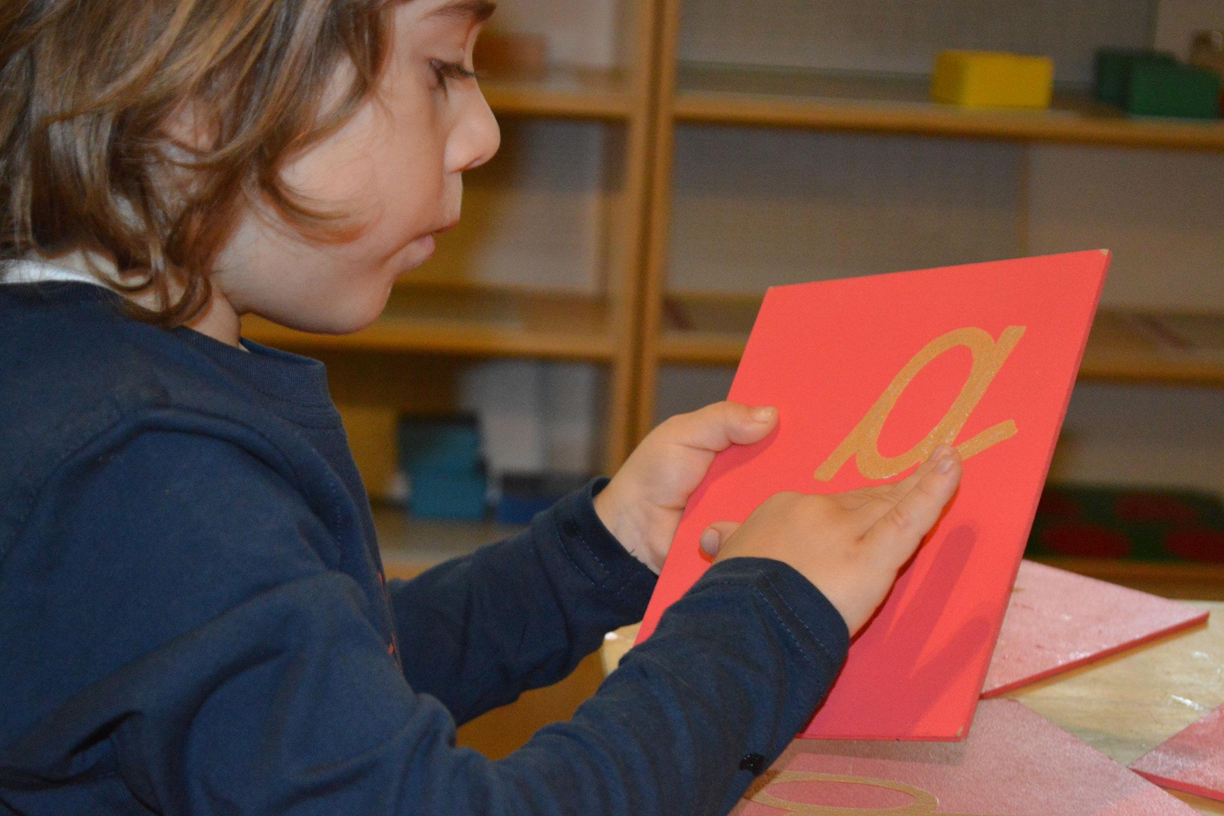 Child tracing Montessori sandpaper letter material