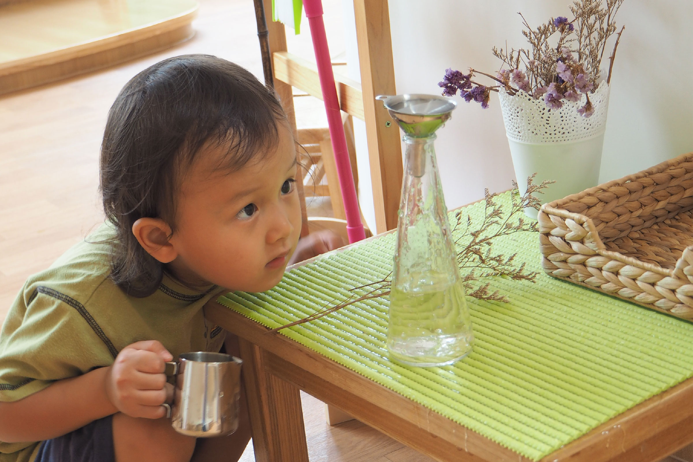 Toddler pouring activity in Montessori classroom