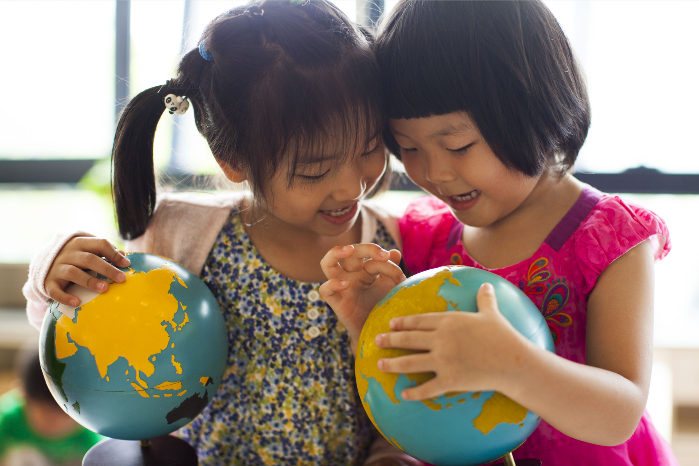 Two children holding globes