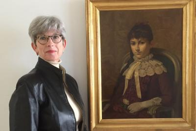 Helen Henny next to portrait of Maria Montessori