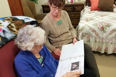 Elderly woman and carer reading memory book