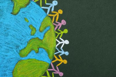 Chalk drawing children holding hands on globe